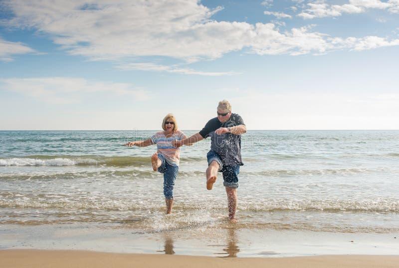 Pares mayores en el amor que camina en la playa que se divierte en un día soleado imagen de archivo