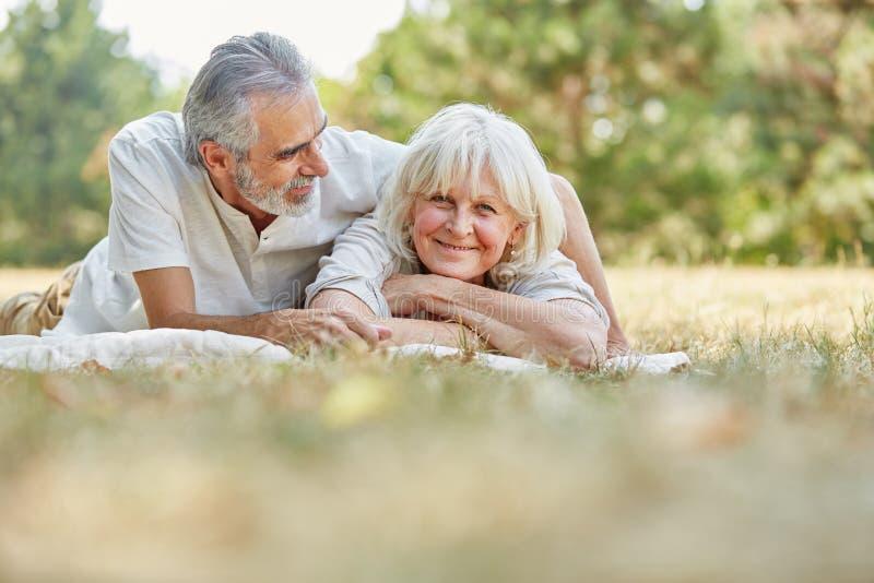 Pares mayores en el amor que se relaja en los gras foto de archivo libre de regalías