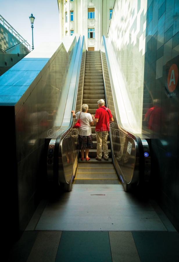 Pares mayores en escalera móvil subterráneo fotos de archivo