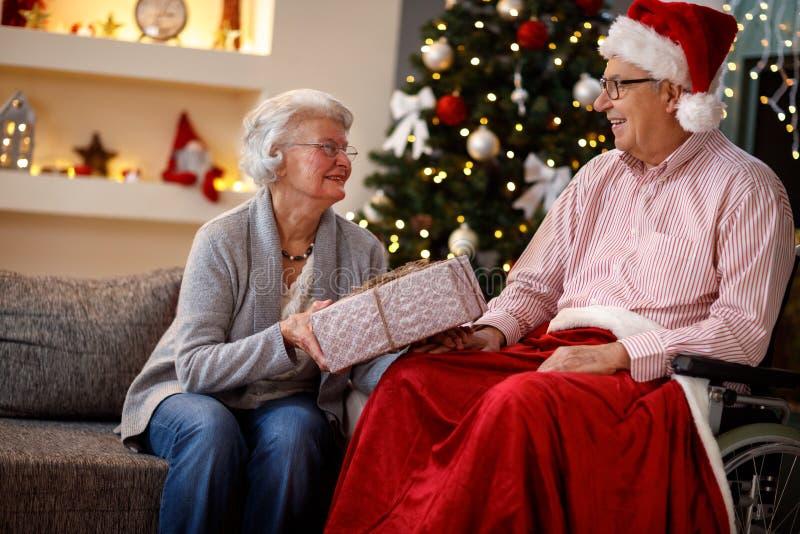 Pares mayores en la Navidad que comparte los regalos de la Navidad foto de archivo