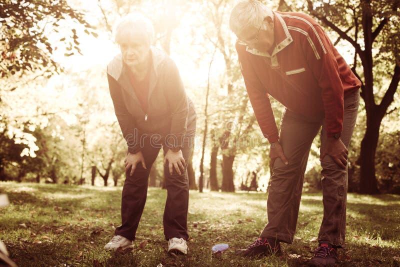 Pares mayores en la ropa de los deportes que descansa después de ejercicio imagen de archivo