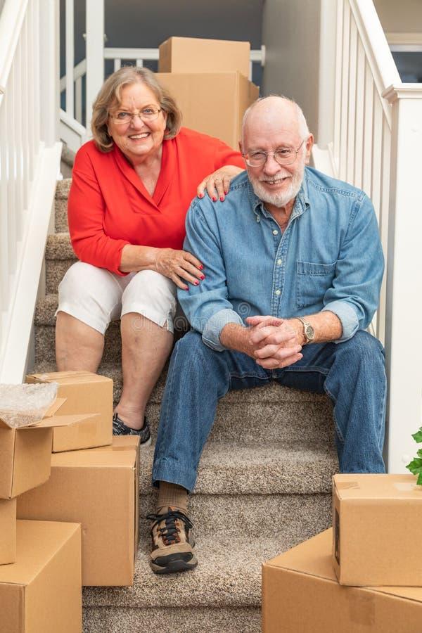 Pares mayores en las escaleras rodeadas moviendo las cajas foto de archivo libre de regalías