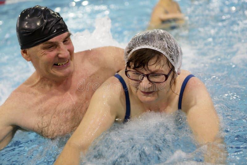 Pares mayores en piscina foto de archivo