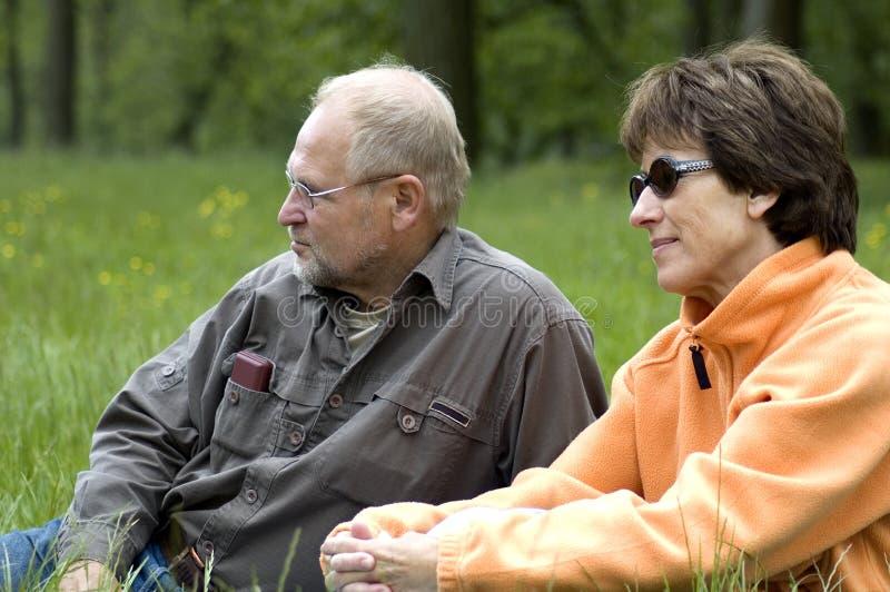 Pares mayores en un grassfield verde fotografía de archivo