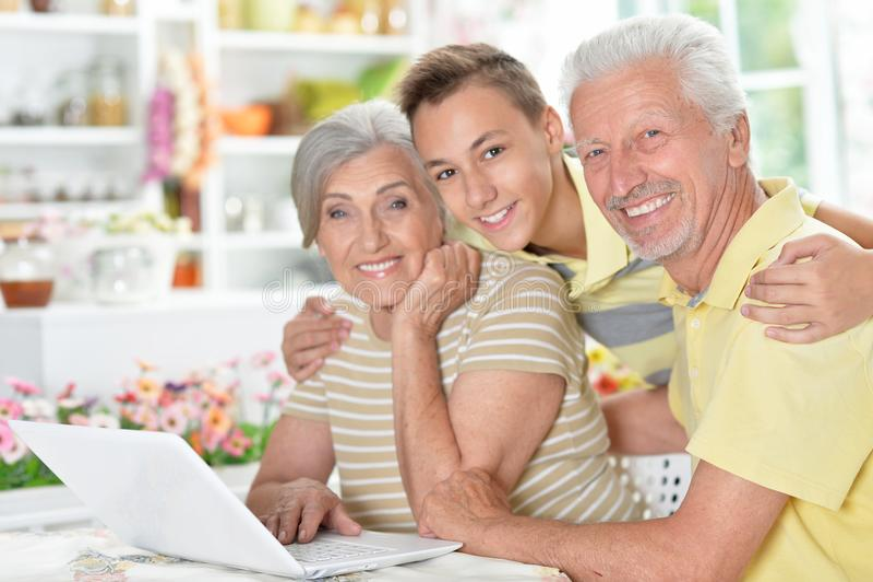 Pares mayores felices con el nieto que usa el ordenador portátil fotografía de archivo