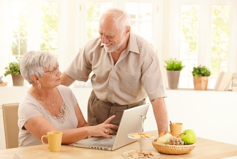 Pares mayores felices con el ordenador en el país foto de archivo