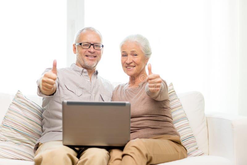 Pares mayores felices con el ordenador portátil en casa foto de archivo