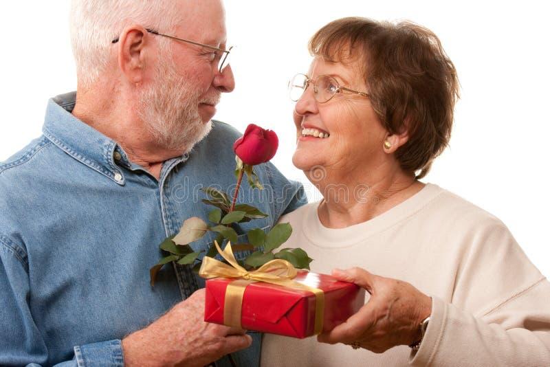 Pares mayores felices con el regalo y Rose roja imagen de archivo