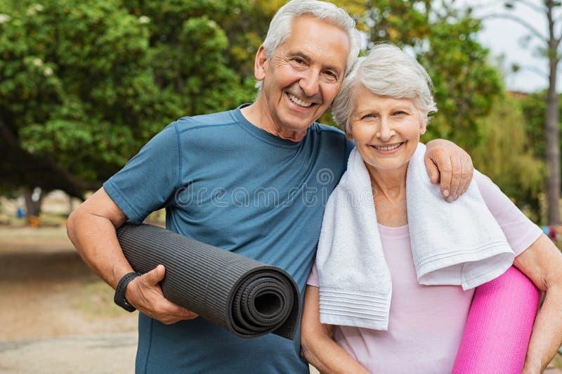 Pares mayores felices con la estera de la yoga fotografía de archivo libre de regalías