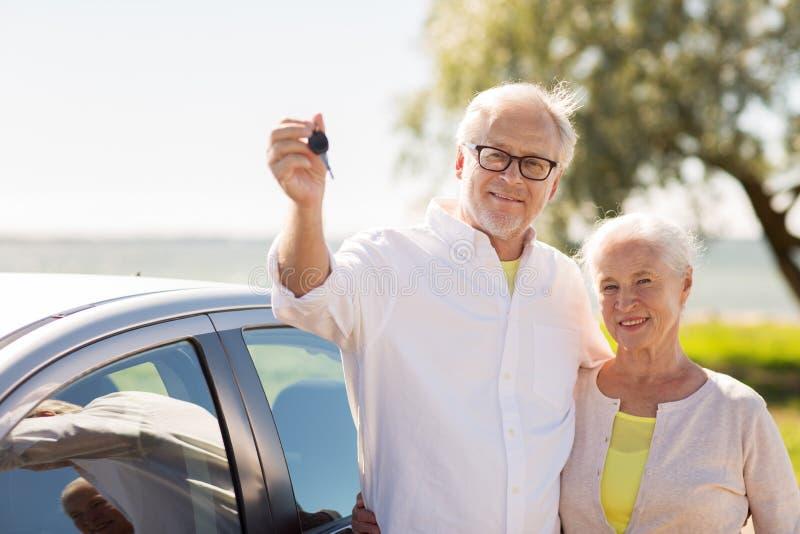Pares mayores felices con llave del coche en la playa imagenes de archivo