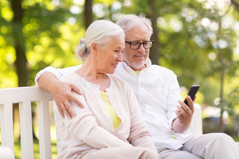 Pares mayores felices con smartphone en el parque fotos de archivo