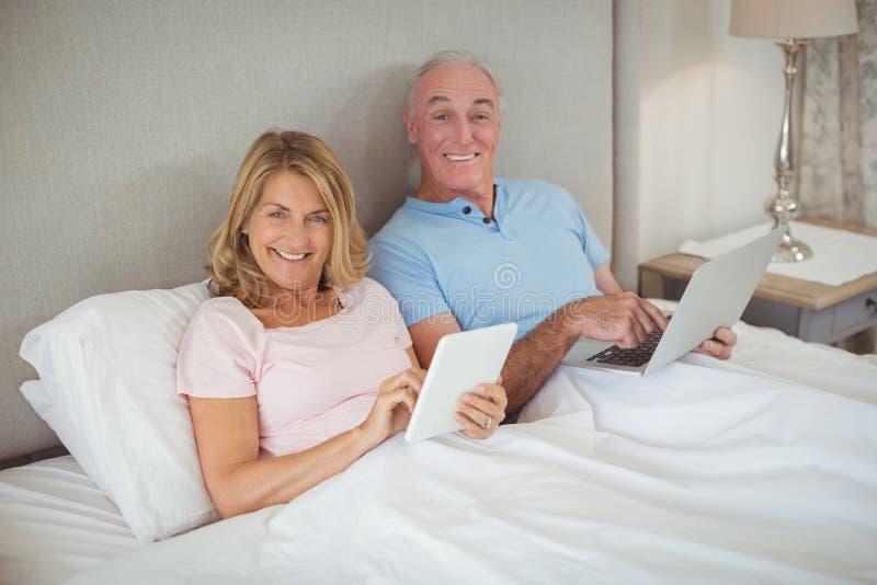 Pares mayores felices en cama usando el ordenador portátil y la tableta digital fotos de archivo