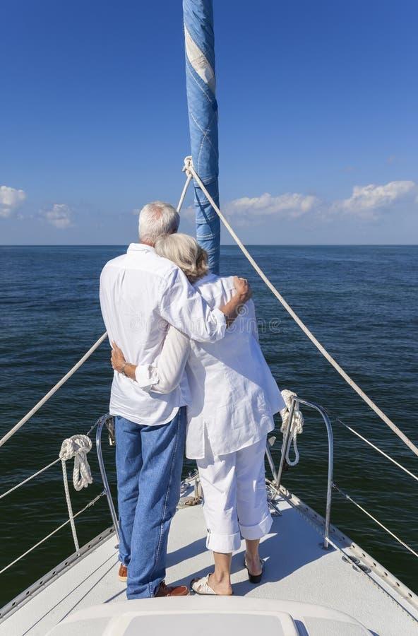 Pares mayores felices en frente de un barco de vela foto de archivo