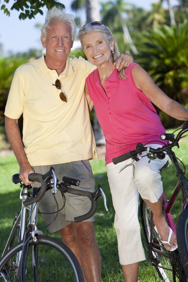 Pares mayores felices en las bicicletas en parque verde imagen de archivo libre de regalías