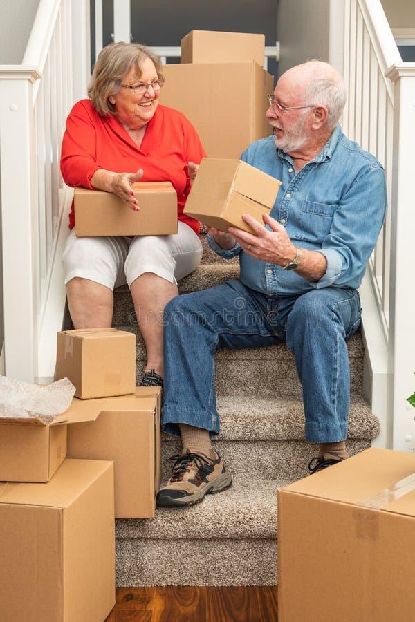 Pares mayores felices en las escaleras rodeadas moviendo las cajas imagen de archivo libre de regalías