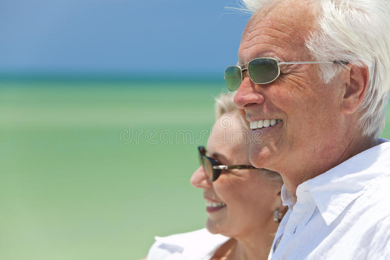 Pares mayores felices por el mar en una playa tropical