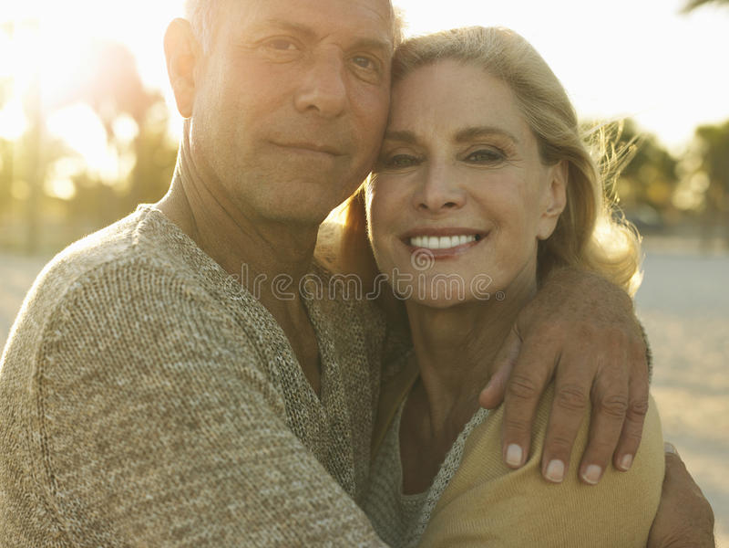 Pares mayores felices que abrazan en la playa fotografía de archivo libre de regalías