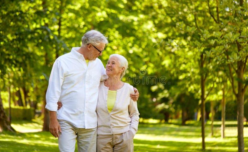 Pares mayores felices que abrazan en parque de la ciudad fotos de archivo