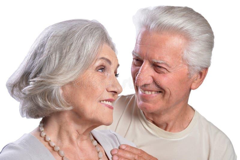 Pares mayores felices que abrazan y que presentan en el fondo blanco foto de archivo