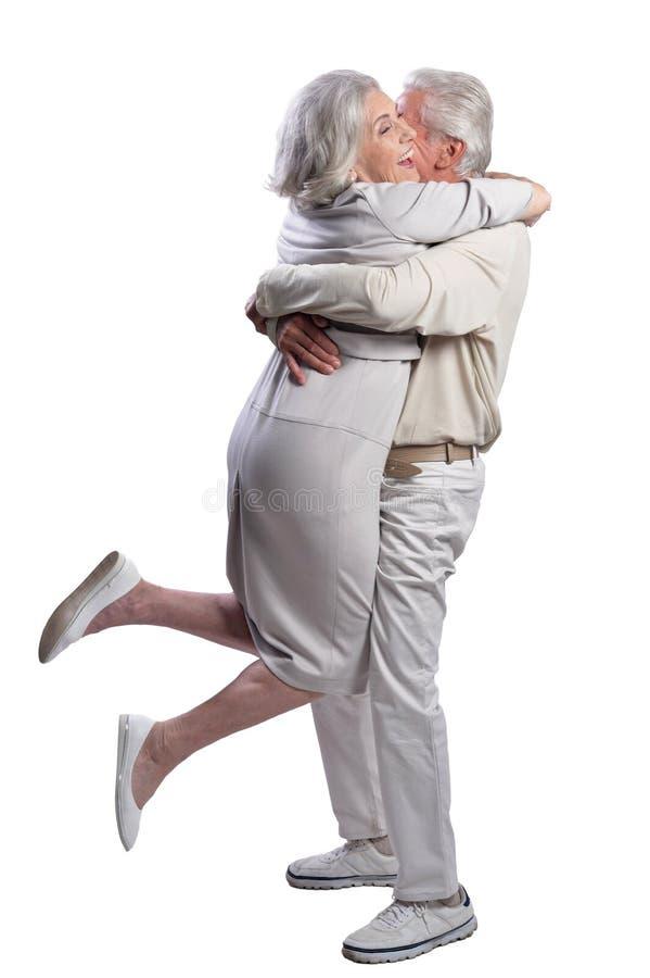Pares mayores felices que abrazan y que presentan en el fondo blanco fotos de archivo libres de regalías