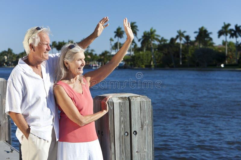Pares mayores felices que agitan afuera por el mar imagen de archivo libre de regalías