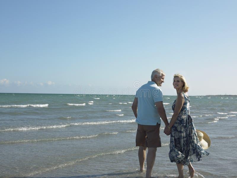 Pares mayores felices que caminan en la playa imagenes de archivo
