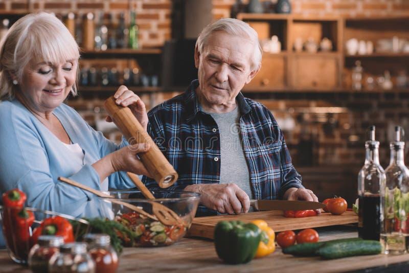 Pares mayores felices que cocinan junto en casa foto de archivo libre de regalías