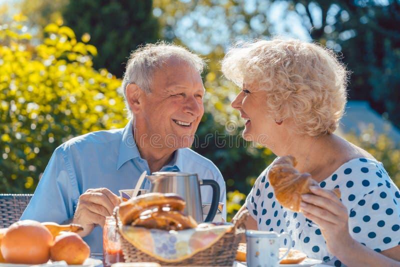 Pares mayores felices que comen el desayuno en su jardín al aire libre foto de archivo