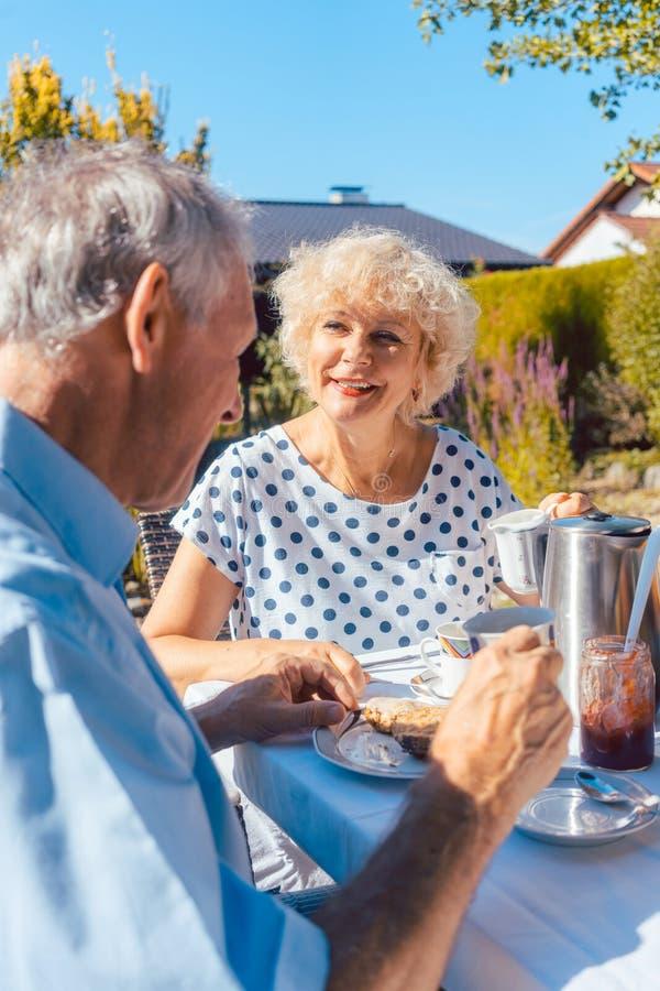 Pares mayores felices que comen el desayuno en su jardín al aire libre imagen de archivo libre de regalías