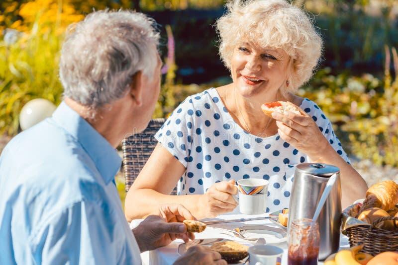 Pares mayores felices que comen el desayuno en su jardín al aire libre yo fotos de archivo