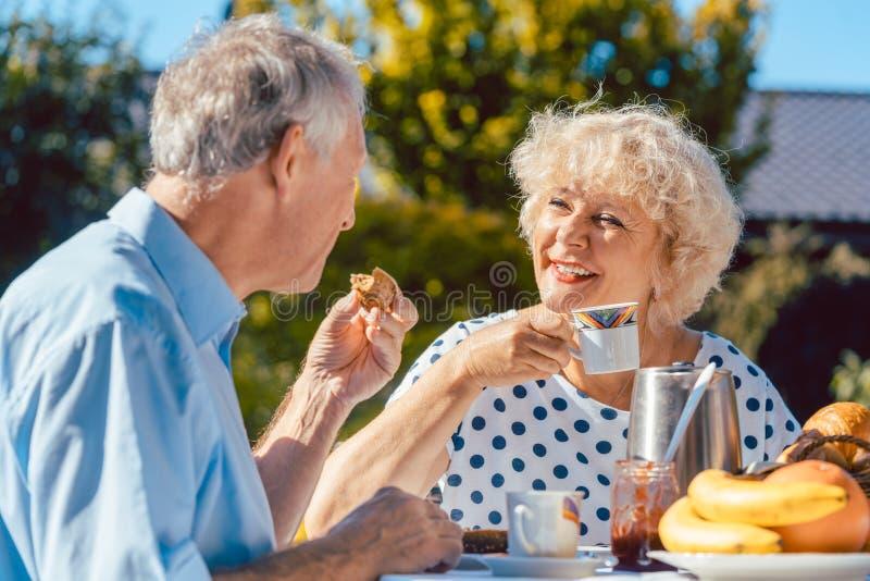 Pares mayores felices que comen el desayuno en su jardín al aire libre yo fotos de archivo libres de regalías