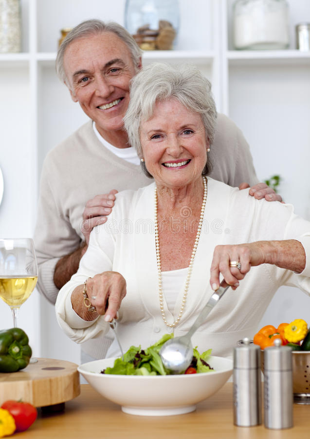 Pares mayores felices que comen una ensalada en la cocina fotografía de archivo