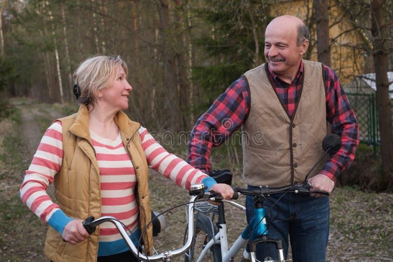 Pares mayores mayores felices que completan un ciclo en parque foto de archivo