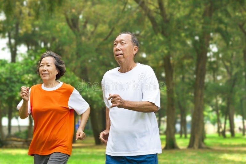 Pares mayores felices que corren junto imagen de archivo