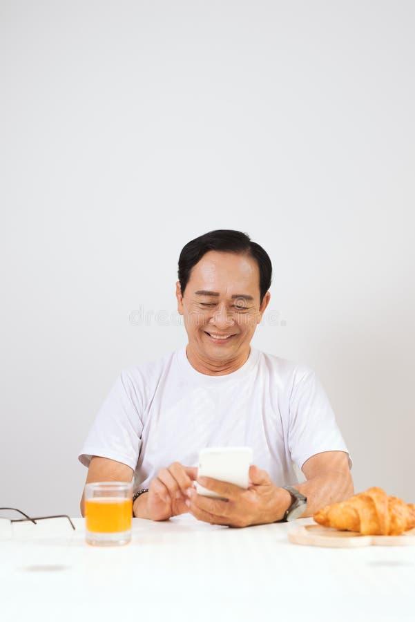 Pares mayores felices que desayunan el cruas?n en casa y que beben el zumo de naranja, usando smartphone fotografía de archivo