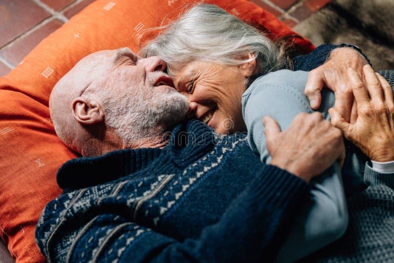 Pares mayores felices que duermen en el piso que se abraza en una noche fría Mujer mayor sonriente que duerme en los brazos de su fotos de archivo