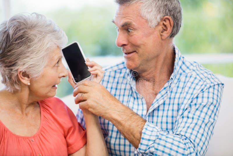 Pares mayores felices que escuchan el smartphone foto de archivo libre de regalías