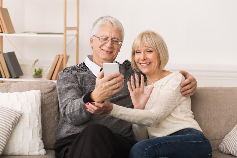 Pares mayores felices que hacen la llamada video y que agitan al visitante fotos de archivo