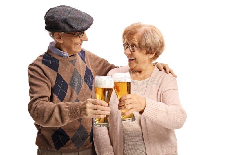 Pares mayores felices que hacen una tostada con los vasos de cerveza imagen de archivo