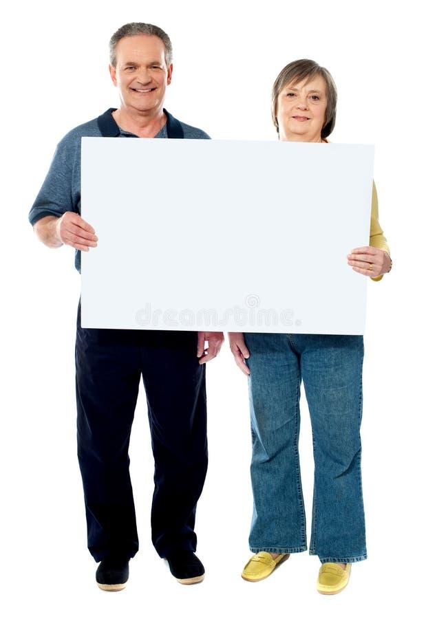 Pares mayores felices que llevan a cabo un cartel blanco imagen de archivo libre de regalías