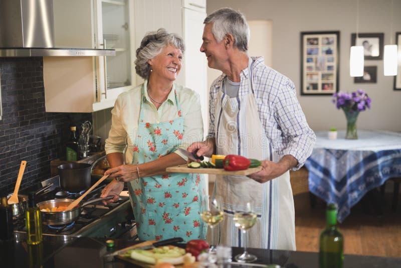 Pares mayores felices que miran uno a que prepara la comida junta en cocina imagen de archivo libre de regalías