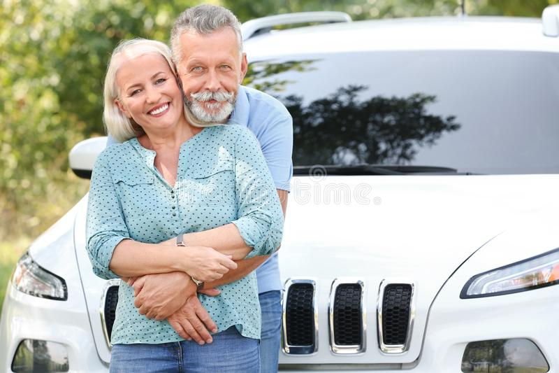 Pares mayores felices que presentan cerca del coche imágenes de archivo libres de regalías