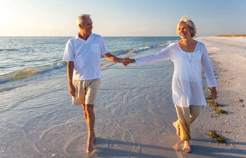 Pares mayores felices que recorren sosteniendo la playa tropical de las manos imagenes de archivo