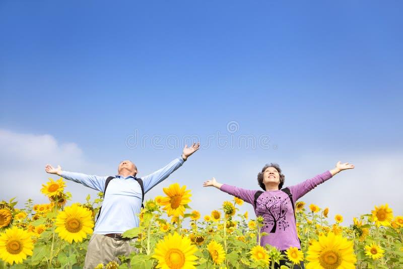 Pares mayores felices que se colocan en el jardín foto de archivo libre de regalías