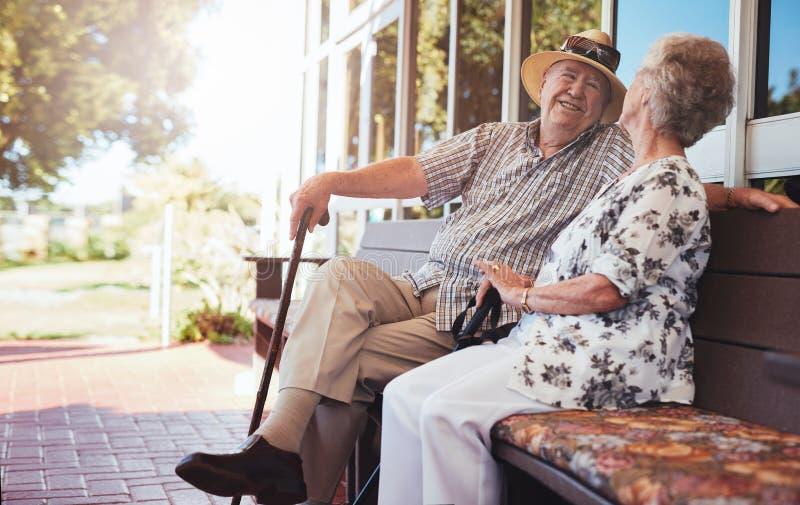 Pares mayores felices que se relajan en banco fuera de su casa fotos de archivo