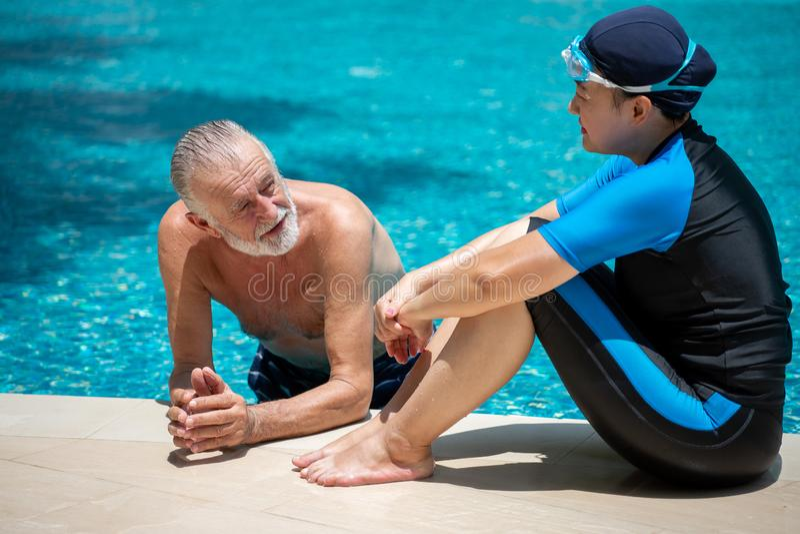 Pares mayores felices que se relajan en piscina junto Padre y ni?o que juegan junto retiro, entrenamiento, aptitud, deporte, ejer foto de archivo libre de regalías