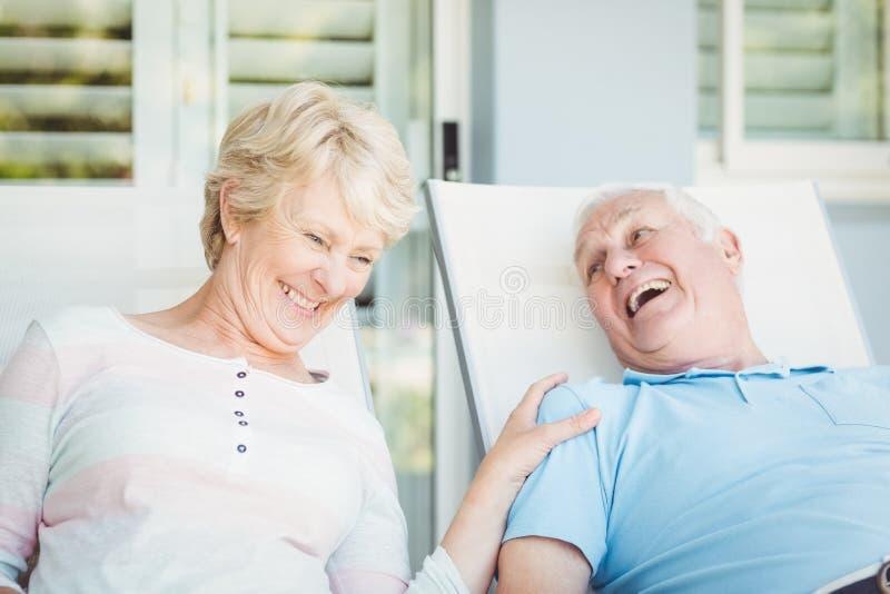 Pares mayores felices que se relajan en sillón fotografía de archivo libre de regalías