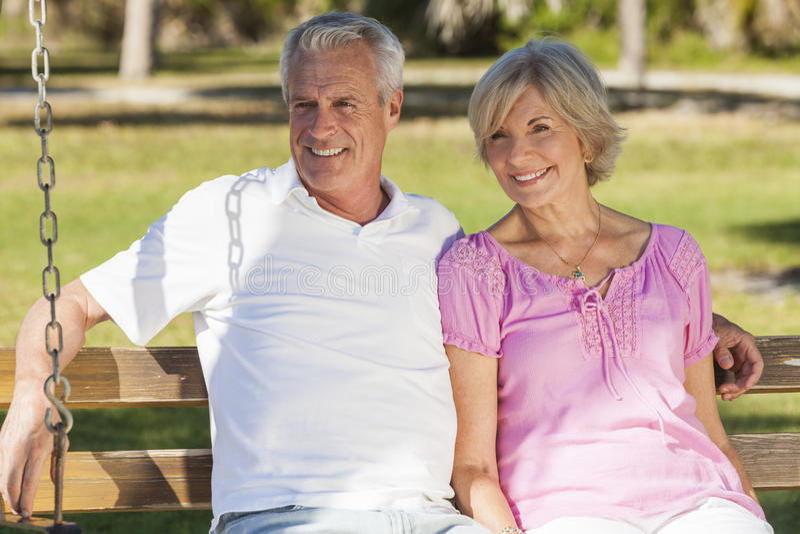 Pares mayores felices que se sientan en banco en sol foto de archivo