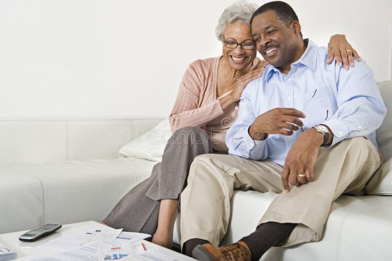 Pares mayores felices que se sientan en el sofá imagenes de archivo