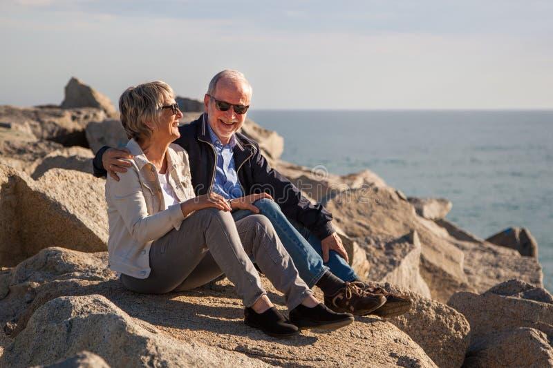 Pares mayores felices que se sientan en rocas por el mar foto de archivo